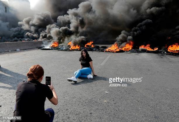 Lebanese demonstrators pose for pictures in front of a tire fire during a protest against dire economic conditions on October 18 2019 in Nahr Ibrahim...