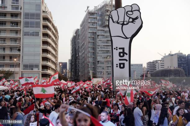 "Lebanese demonstrators raise a large clenched fist with ""revolution"" written on it at the Martyrs' Square in the centre of the capital Beirut on..."