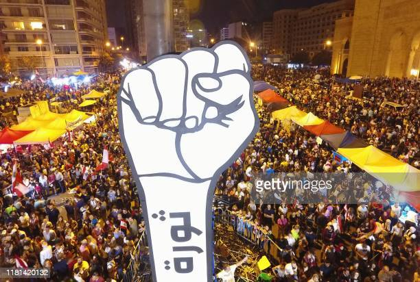 Lebanese demonstrators raise a large clenched fist with the slogan revolution written on it in Arabic in Beirut's Martyrs Square during continuing...