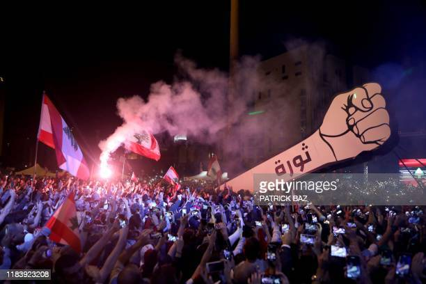 TOPSHOT Lebanese demonstrators raise a new giant sign of a fist that bears the Arabic word revolution on it in the Lebanese capital Beirut's Martyr's...