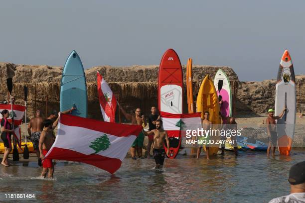 Lebanese demonstrators raise the national flag as they protest on Zireh islet off the coast of the southern city of Saida which they reached on...