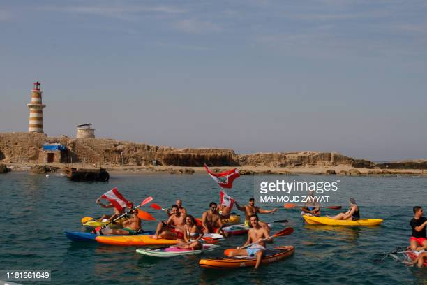 Lebanese demonstrators raise the national flag as they protest on canoes and paddleboards near Zireh islet off the coast of the southern city of...