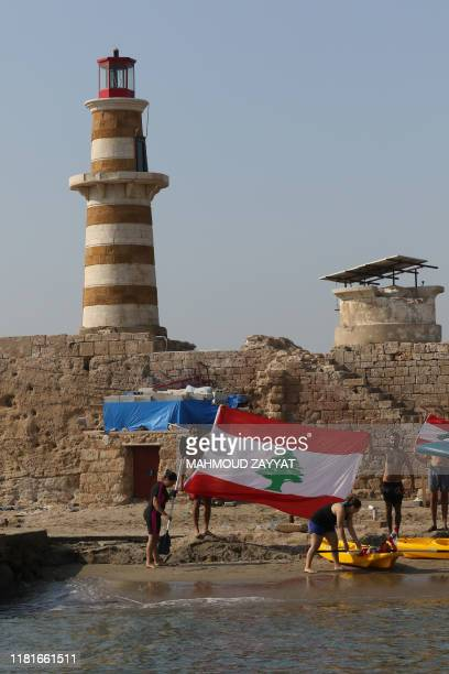 Lebanese demonstrators raise the national flag as they protest under a lighthouse on Zireh islet off the coast of the southern city of Saida which...