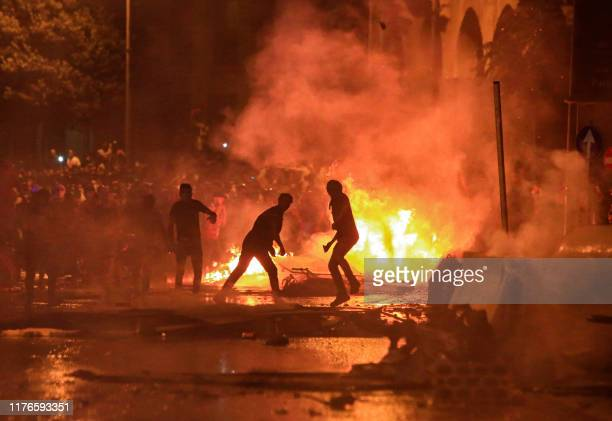 Lebanese demonstrators stand by a fire a makeshift barricade amidst clashes with security forces during a mass protest at Riad alSolh Square in the...