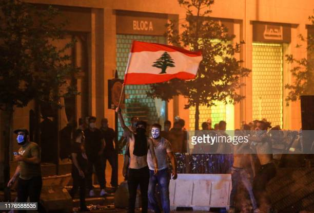 Lebanese demonstrators stand with a national flag behind a makeshift barricade amidst clashes with security forces during a mass protest at Riad...