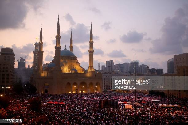 TOPSHOT Lebanese demonstrators take part in a rally outside the Mohammad alAmin mosque and the nearby Maronite Cathedral of St George in the capital...