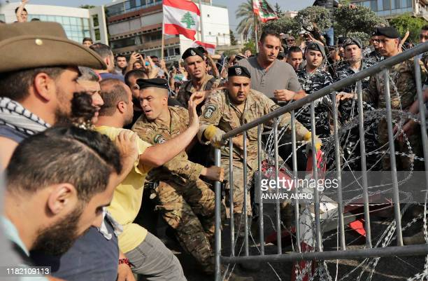 Lebanese demonstrators try to remove the barbed-wire and metal rail, placed by anti-riot police , on the road leading to the Presidential Palace in...