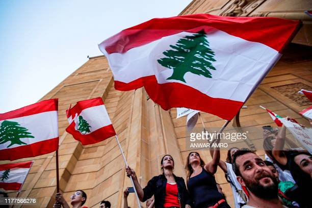 Lebanese demonstrators wave national flags as they stand outside the Mohammad al-Amin mosque during a demonstration on the sixth day of protest...