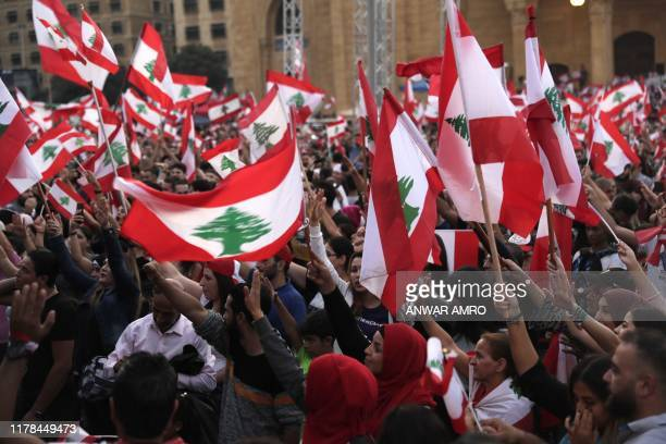 Lebanese demonstrators wave national flags at the Martyrs' Square in the centre of the capital Beirut on October 27 during ongoing anti-government...