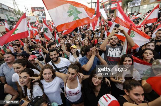 Lebanese demonstrators wave national flags on a highway linking Beirut to north Lebanon in Zouk Mosbeh on October 19 a day after demonstrations swept...