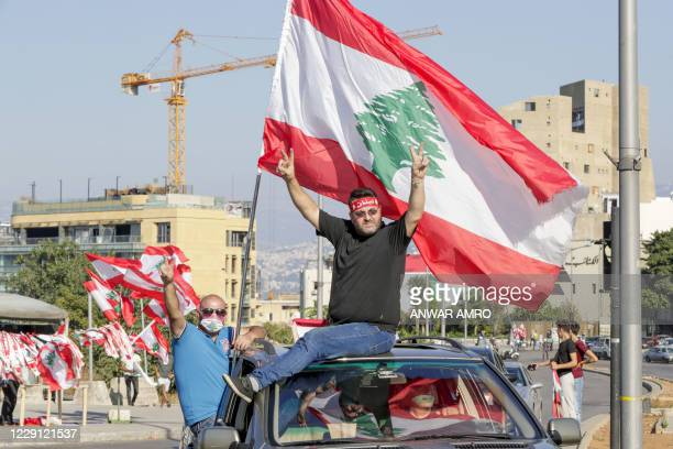 Lebanese demonstrators wave the national flag as they drive to a demonstration, marking the first anniversary of a non-sectarian protest movement, in...