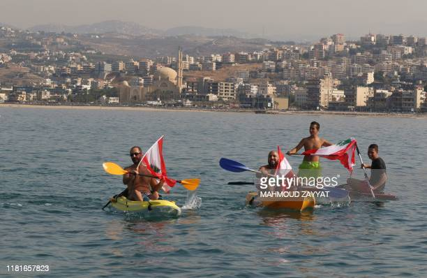 Lebanese demonstrators wave the national flag as they protest on canoes and paddleboards off the coast of the southern city of Saida on November 11...