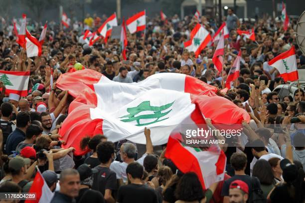 Lebanese demonstrators wave the national flag during a protest against dire economic conditions in downtown Beirut on October 18, 2019. - Public...