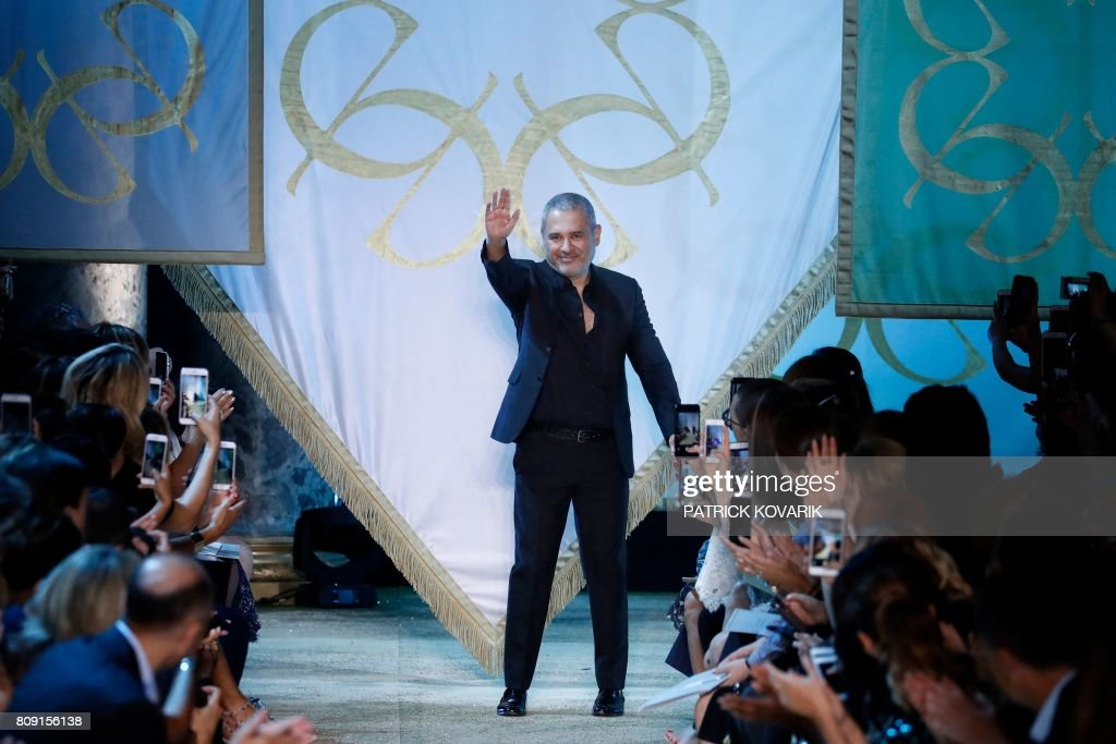 Lebanese designer Elie Saab acknowledges the audience at the end of the 2017-2018 fall/winter Haute Couture collection in Paris on July 5, 2017. / AFP PHOTO / Patrick KOVARIK
