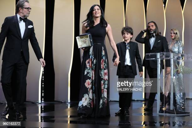 TOPSHOT Lebanese director and actress Nadine Labaki poses on stage next to Syrian actor Zain alRafeea and her husband Lebanese producer Khaled...