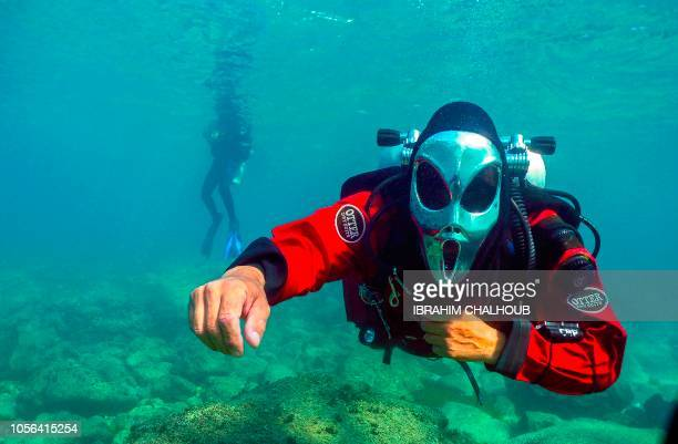 Lebanese divers dressed in Halloween masks dive off the coast of Batroun city north of Beirut Lebanon on November 2 2018