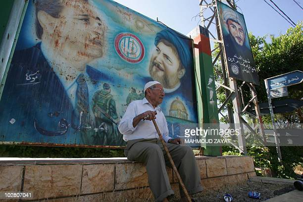 Lebanese elderly man sits under a billboard bearing portraits of the Shiite Amal movement leaders the missing cleric Sayyed Mussa alSadr and current...