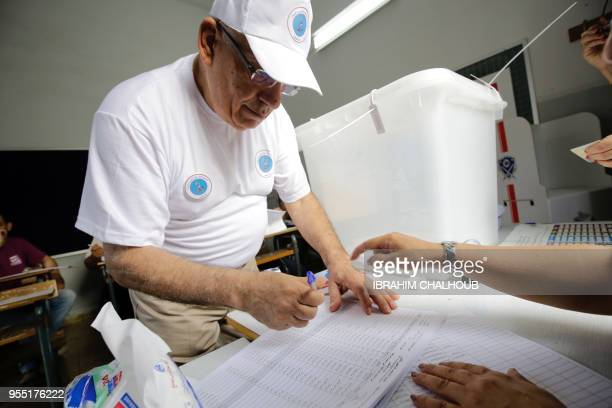 A Lebanese election registrar helps a man register after voting in the first parliamentary election in nine years in the Mina district of the...