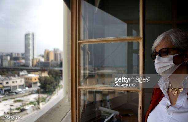 Lebanese employee at a chemical company wearing a protective mask looks at the empty city amid the COVID-19 outbreak, in the capital Beirut on March...