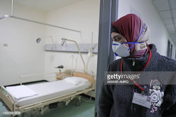 Lebanese employee wearing a protective mask looks at a bed in a ward where the first case of coronavirus in the country is being treated, at the...