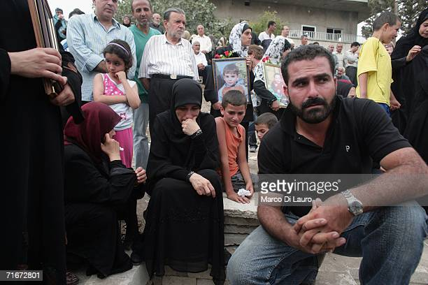 Lebanese family is seen at the grave yard as they just buried one of their relative one of the victims of the Qana massacre during the funeral on...