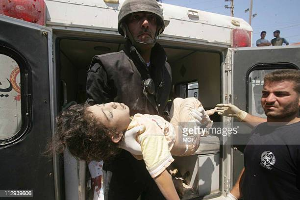 A Lebanese firefighter carries the body of a child to a hospital in the port city of Tyre Lebanon Sunday July 30 after an Israeli air strike killed...