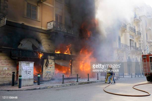 Lebanese firefighters attempt to extinguish the fire at a bank branch set ablaze by demonstrators following the funeral of protester Fawaz alSamman...