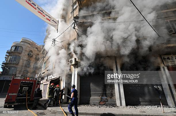 Lebanese firefighters extinguish a flame in a building during clashes between Army soldiers and Islamist gunmen in the historic market of the...