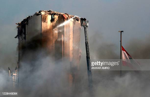 Lebanese firefighters stand on a ladder amid billowing smoke as they extinguish the remaining flames at the seaport of Beirut, on September 11 a day...