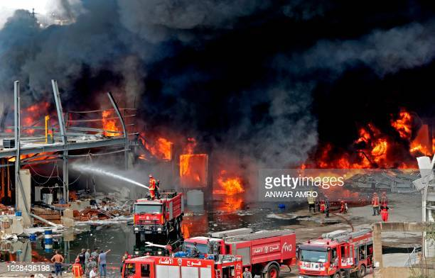 Lebanese firefighters try to put out a fire that broke out at Beirut's port area, on September 10, 2020. - Thick black columns of smoke rose into the...