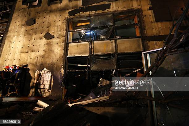 Lebanese firemen exit a damaged building following an explosion near a major bank in the western part of the Lebanese capital Beirut late on June 12...