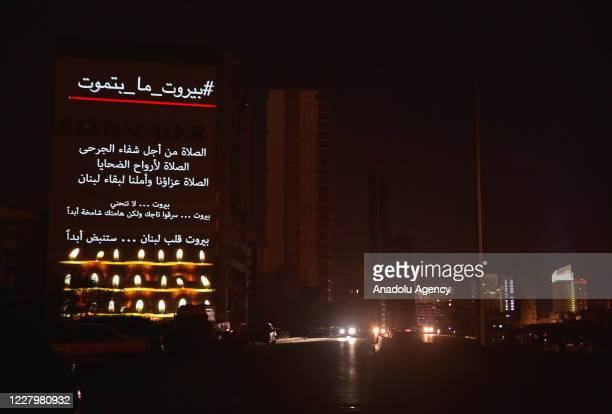 Lebanese flag and messages are reflected on the wall of a building to commemorate those who lost their lives after the deadly explosion at the Port...