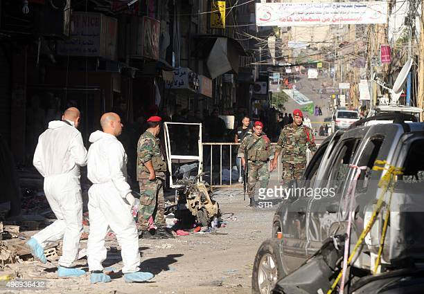 Lebanese forensic police and security forces inspect the site of a twin bombing attack that rocked a busy shopping street in the area of Burj...