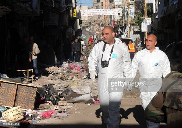 Lebanese forensic police and security forces investigate the site of a twin bombing attack that rocked a busy shopping street in the area of Burj...