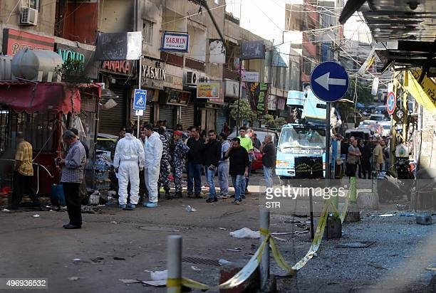 Lebanese forensic police, security forces and members of the Hezbollah movement inspect the site of a twin bombing attack that rocked a busy shopping...