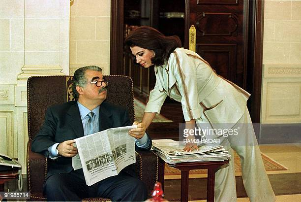 Lebanese former and likely next Prime Minister Rafiq Hariri reads a copy of AlMustakbal the paper his owns while his wife Nazeq looks on at their...