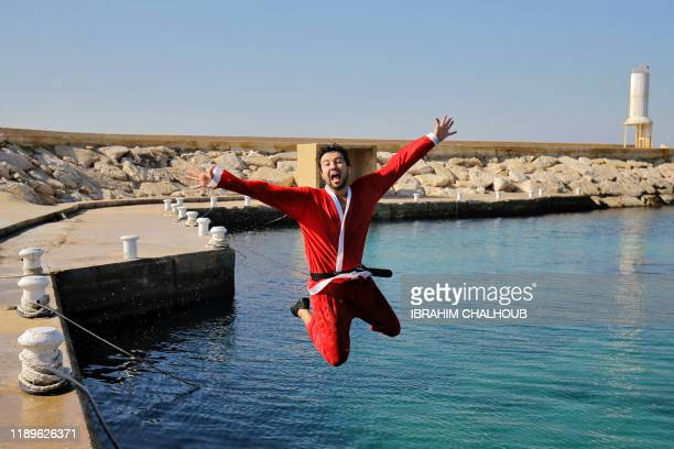 A Lebanese freediver wears a Father Christmas reacts as he jumps into the water off the coast of the northern city of Batroun on December 19 2019