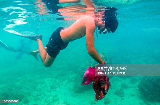 Lebanese Freedivers take part in the International Coastal CleanUp Day in the northern port city of Tripoli on September 14 2018