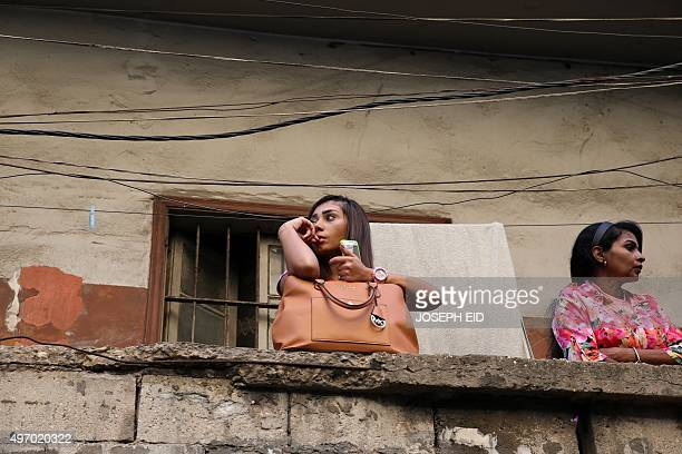 Lebanese girls looks on as municipality workers clear debris from the site of a twin bombing attack in the area of Burj al-Barajneh in Beirut's...