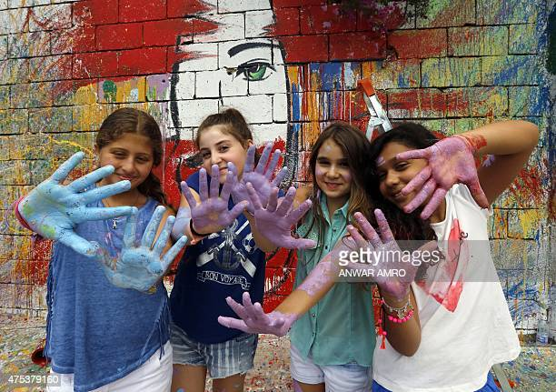 Lebanese girls shows their hands as they paint graffitis on a wall during a festival organised in the profit of the Lebanese Autism Society NGO on...