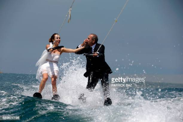 Lebanese groom Tommy kisses the hand of his bride Nadine's while water skiing dressed in their wedding clothes in the waters off the bay of Jounieh...