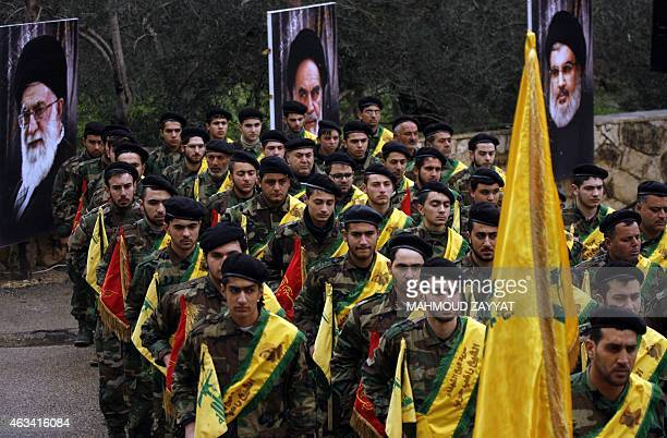 Lebanese Hezbollah fighters march near portraits of Iran's Supreme Leader Ayatollah Ali Khamenei founder of Iran's Islamic Republic late Ayatollah...