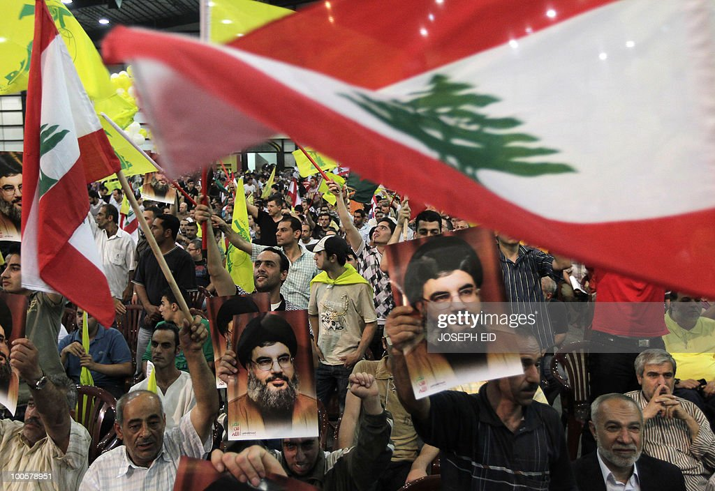 Lebanese Hezbollah supporters wave Lebanese and party (yellow) flags while holding pictures of party leader Hassan Nasrallah during a ceremony marking the 10th anniversary of Israel's withdrawal from southern Lebanon in southern Beirut on May 25, 2010. Nasrallah said that his militants are capable of wiping out Israel's navy and any other ships heading to Israel in the event of a new war with the Jewish state.