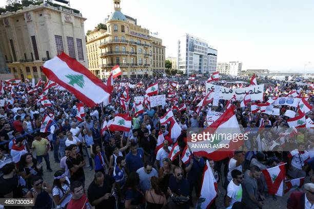 Lebanese hold banners and flags during a mass rally against a political class seen as corrupt and incapable of providing basic services on August 29...