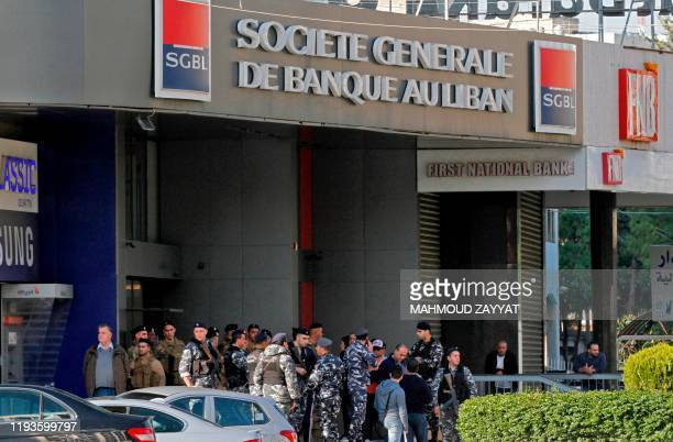 Lebanese Internal Security Forces stand guard at the entrance of a bank as antigovernment protesters demonstrate in the southern city of Sidon on...