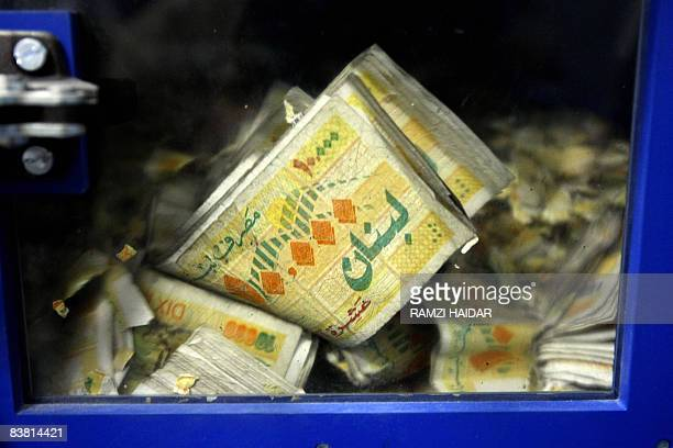 Lebanese lira bills are damaged in a special machine at Lebanon's Central Bank in Beirut on November 24, 2008. Lebanon for now has managed to steer...