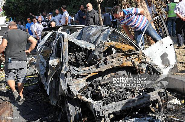Lebanese look at a burnt vehicle on August 24 2013 next to the site of one of the two explosions that struck the northern city of Tripoli the day...