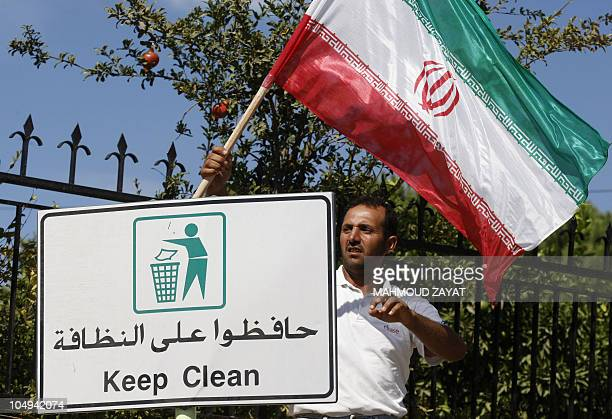 A Lebanese man attaches an Iranian flag on a road sign in the southern Lebanese town of Kfar Kila on October 7 2010 as Lebanon prepares for an...