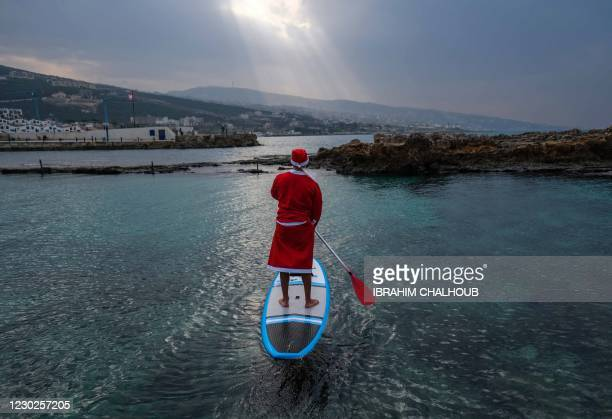Lebanese man dressed with a Santa Claus outfit rides on a standup paddle in Lebanon's northern coastal city of Batroun on December 22, 2020.