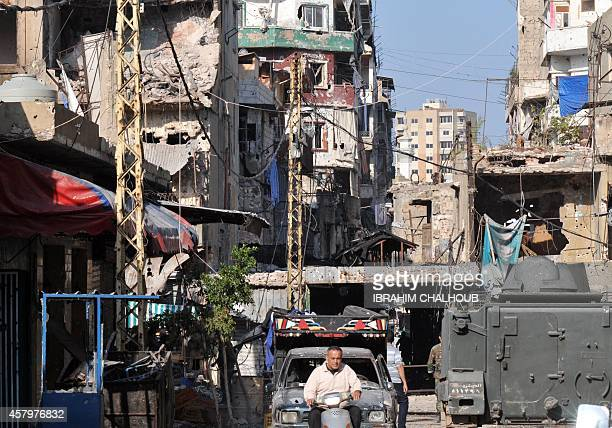 A Lebanese man drives a scooter down a damaged street in Tripoli's Bab alTabbaneh Sunni neighbourhood on October 28 2014 after three days of fierce...